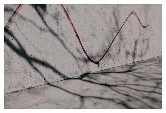 Contemporary art street photography of shadows and a red line on a wall on the street in London from See Flowers In Hell by artist Melissa Spiccia